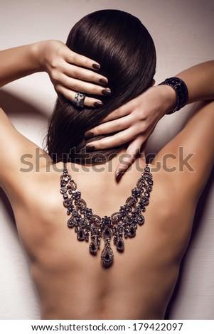woman with bijou on naked back - stock photo