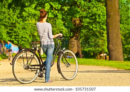Woman with bike talking on mobile phone in park - stock photo