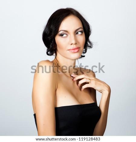 Woman with black hair posing in studio - stock photo