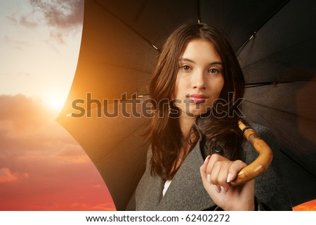 Woman with black umbrella over scenic sunset sky background. - stock photo