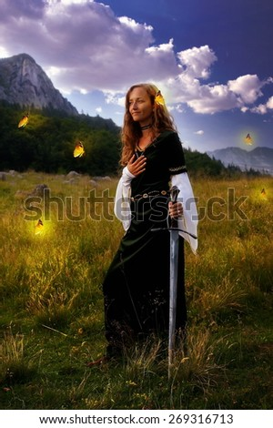 woman with blonde hair in historical dress is posing in an enchanting open landscape with trees and a mountain meadow, with a hand-to-heart gesture and mystical medieval sword. with yellow butterflies - stock photo