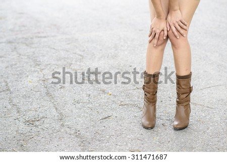 Woman with boot waiting on the old asphalt road - stock photo