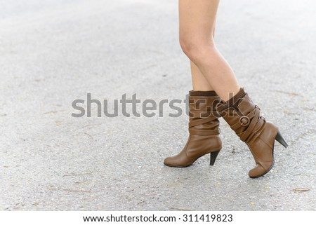 Woman with boot walking on the asphalt road - stock photo