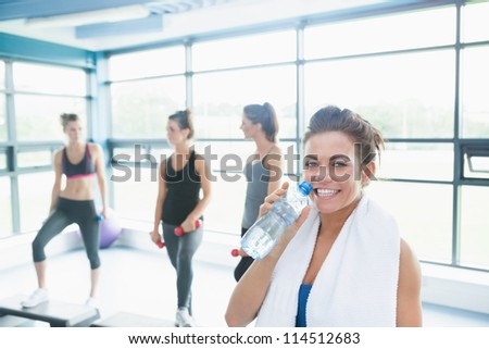 Woman with bottle of water in aerobics class in gym - stock photo