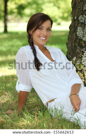 Woman with braid sitting on the grass - stock photo