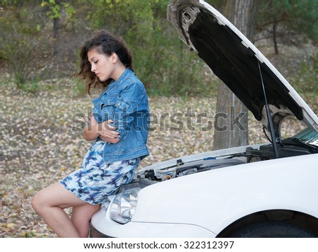 Woman with broken car wait on road  - stock photo