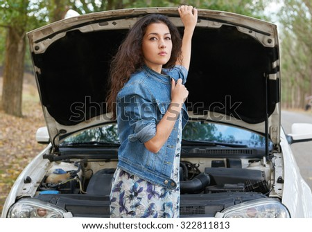 Woman with broken car wait service on road - stock photo