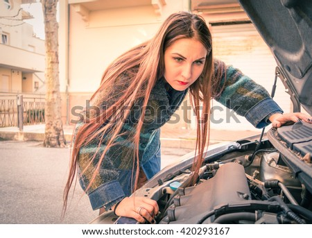 Woman with broken down car looking to engine - Young female driver and unexpected automobile breakdown along road trip - Concept of human stress in everyday life with dramatic tones and vignetting - stock photo