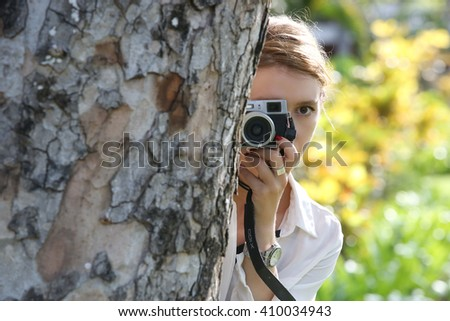 Woman with camera hiding behind the tree - stock photo