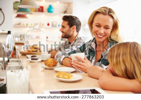 Woman with child in cafe - stock photo