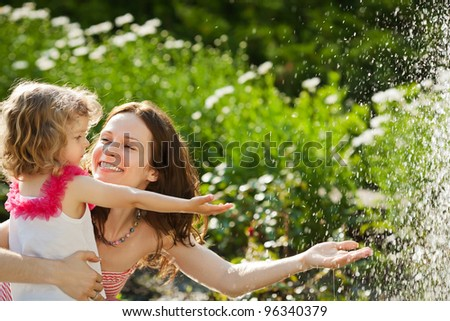 Woman with child playing against splashes of water in the summer - stock photo