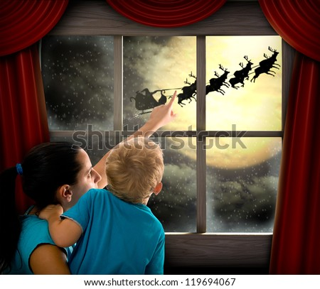 Woman with child pointing at Santa Claus on sky - stock photo