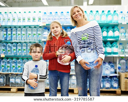 Woman with children is holding a bottle drinking water in shop - stock photo