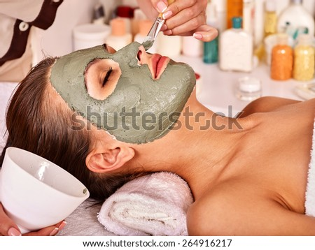 Woman with clay facial mask in beauty spa. Close up. - stock photo