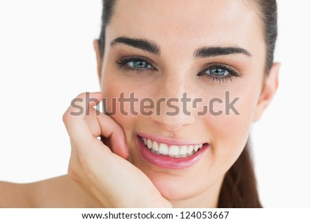 Woman with clear eyes looking at camera while touching her face and smiling - stock photo
