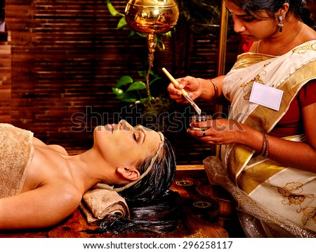 Woman with closed eyes having facial mask at ayurveda spa. - stock photo
