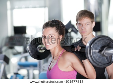 woman with coach  doind exercises with bar - stock photo