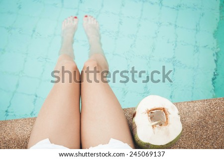 Woman with coconut . Female legs in the pool water - stock photo