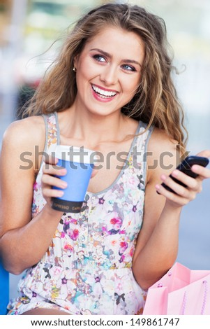 Woman with coffee and mobile phone - stock photo