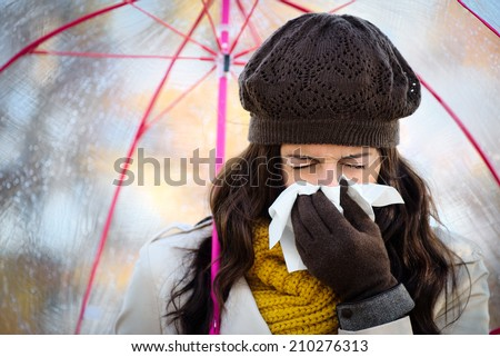 Woman with cold or flu coughing and blowing her nose with a tissue under autumn rain. Brunette female sneezing and wearing warm clothes. - stock photo