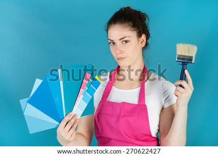 Woman with color samples against blue wall - stock photo