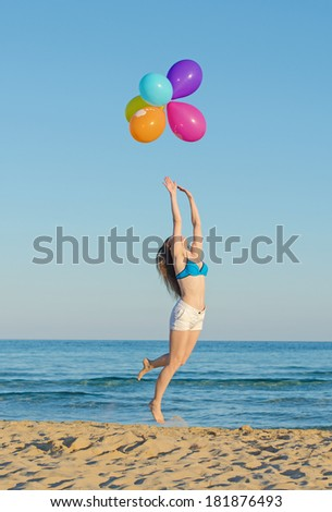 Woman with colorful balloons over sea. - stock photo