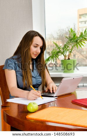 woman with computer sitting at the table - stock photo