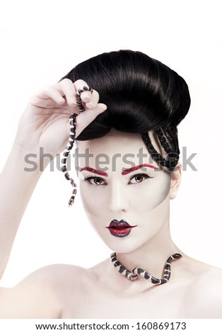 Woman with creative make up and snake in her hands - stock photo