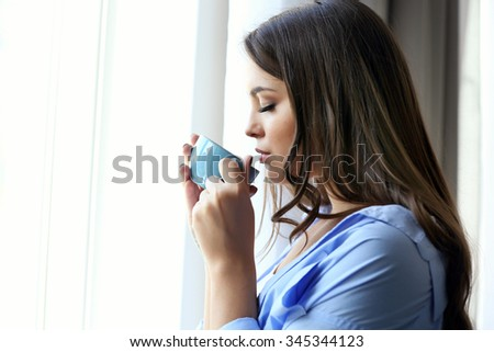 Woman with cup of coffee standing near window in the room - stock photo