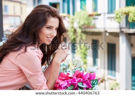 woman with cup of coffee to go against sunny italian house - stock photo