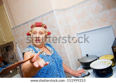 woman with curlers and cosmetic mask, preparing food on the kitchen - stock photo