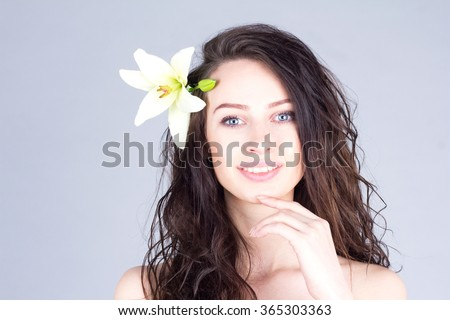 Woman with curly hair and lily in hair smiling with teeth and touching chin. Hawaiian mood. - stock photo
