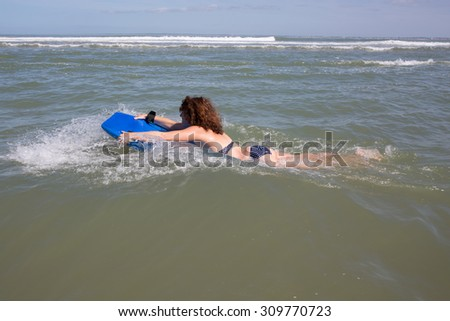 Woman with curly hair at the ocean - stock photo