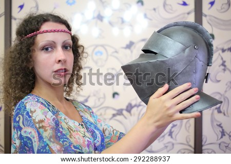 Woman with curly hair holds an antique knights helmet - stock photo