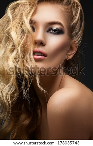 Woman with curly hair on gray background - stock photo