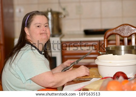 woman with down syndrome in kitchen  - stock photo
