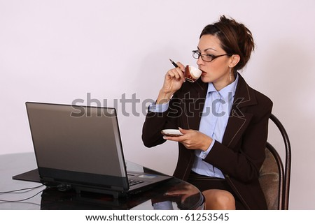 Woman with eyeglasses working on lap top computer and drinking coffee - stock photo