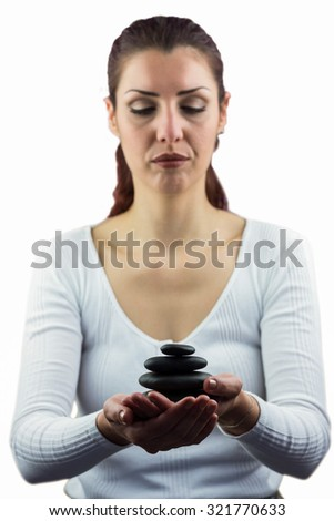 Woman with eyes closed while holding pebbles in her hand - stock photo