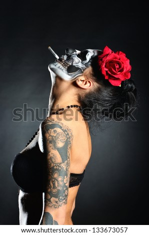 Woman with face-art of scull - stock photo