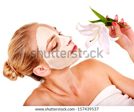 Woman  with facial mask  holding flower. Isolated. - stock photo