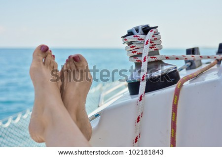 Woman with feet relaxing on a sailboat with lines in background - stock photo