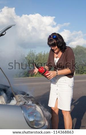 Woman with fire extinguisher near smoking car - stock photo