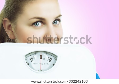 woman with floor scales, isolated against white background - stock photo