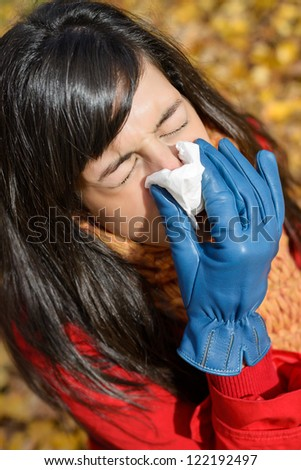Woman with flu or cold sneezing and blowing her nose with a kleenex tissue on cold autumn day. Autumnal illness. - stock photo