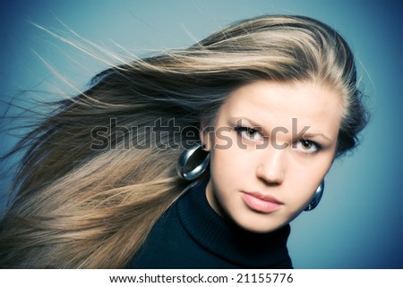 Woman with fluttering hair. On blue background. - stock photo