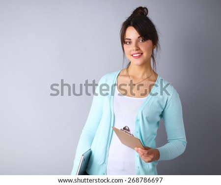 Woman with folder for documents on gray  background - stock photo