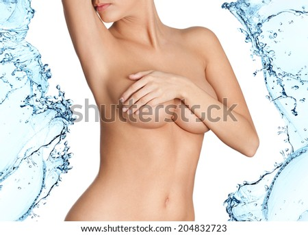 Woman with fresh skin in splashes of water, isolated on white background - stock photo
