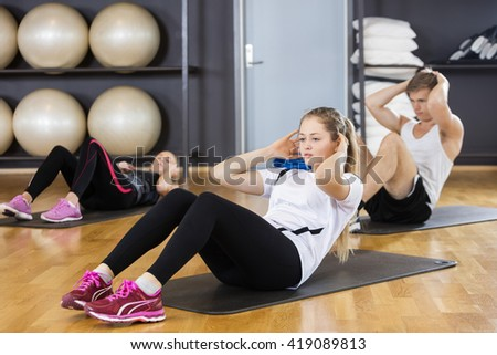 Woman With Friends Doing Situps In Gymnasium - stock photo
