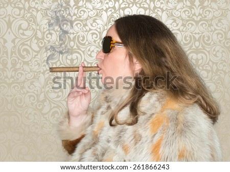 Woman with fur coat and sunglasses smokes a cigar - stock photo