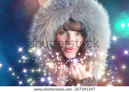 woman with furry hat blowing sparkling stars into the air - stock photo